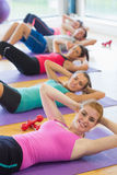 Sporty fitness class doing sit ups on exercise mats Stock Images