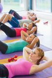 Sporty fitness class doing sit ups on exercise mats Stock Image