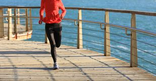 Female runner running on seaside boardwalk Royalty Free Stock Image