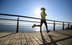 Female runner running on seaside boardwalk during sunrise. Sporty fitness female runner running on seaside boardwalk during sunrise Stock Image