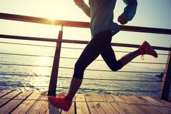 Runner running on seaside boardwalk during sunrise. Sporty fitness female runner running on seaside boardwalk during sunrise Royalty Free Stock Photography