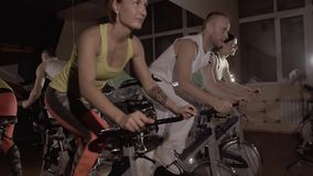 Sporty fitness group of three training on stationary bikes doing exercise synchronously
