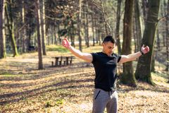Sporty fitness man rising arms at the park. Outdoors royalty free stock photography