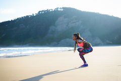 Sporty fitness woman on beach healthy workout. Black fitness woman practicing balance yoga exercise towards the sea during outdoor workout at the beach. Dancing Stock Photography