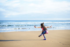 Sporty fitness woman exercising at the beach. Back view of woman practicing balance yoga exercise towards the sea during fitness outdoor workout at the beach Stock Image