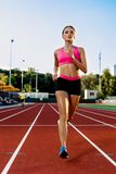Sporty fitness woman jogging on red running track in stadium. Training summer outdoors on running track line with green Stock Image