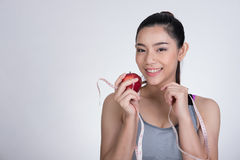 Sporty fitness woman with measuring tape and red apple standing stock photo