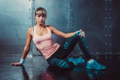 Sporty fitness woman sitting and relaxing on floor Royalty Free Stock Photos