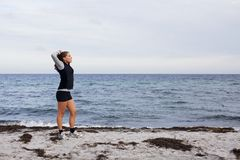 Sporty fitness woman standing on beach after workout Stock Images