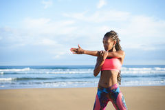 Sporty fitness woman stretching arm at the beach. Fitness woman stretching arm and shoulder at the beach. Black female athlete working out outdoor against the Royalty Free Stock Images