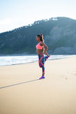 Sporty fitness woman stretching at the beach. Fitness woman stretching leg at the beach. Black female athlete exercising outdoor against the sea Royalty Free Stock Photos