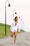 Sporty fitness woman stretching legs before running Royalty Free Stock Photo