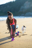 Sporty fitness woman working out at the beach with her dog. Sporty woman lacing sport footwear before running and exercising at the beach with her dog. Black Stock Photography