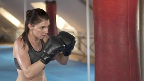 Sporty focused brunette woman training with punching bag in fitness studio. Fierce strength. Slow motion. stock video