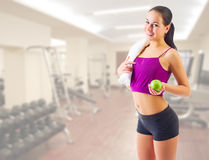 Sporty girl with apple at gym club Royalty Free Stock Image