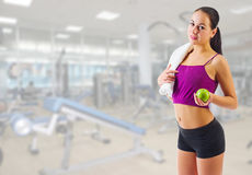 Sporty girl with apple and towel at gym club Stock Photography