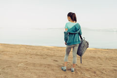 Sporty girl with backpack standing on beach Royalty Free Stock Image