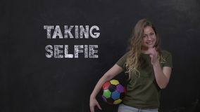 Sporty girl with ball stand on black background and inscription Taking Selfie stock video footage