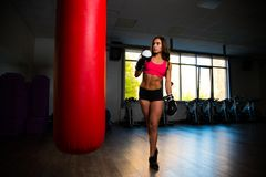 Sporty girl in Boxing gloves next to punching bag. Photo Royalty Free Stock Photos
