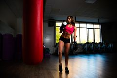 Sporty girl in Boxing gloves next to punching bag. Photo Royalty Free Stock Image