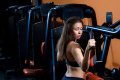 Sporty girl building some muscles on a simulator. Fitness, sport, power-lifting and people concept - a sporty girl building some muscles on a simulator Stock Photo