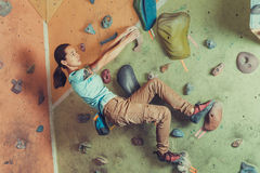 Sporty girl climbing on practice wall Royalty Free Stock Photography