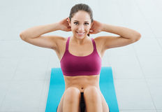 Sporty girl doing abs workout Royalty Free Stock Images
