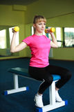Sporty girl doing exercise with dumbbells Stock Images