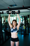Sporty girl doing exercise with dumbbells in the gym Stock Photo