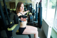 Sporty girl doing exercise with dumbbells in the gym Royalty Free Stock Photos