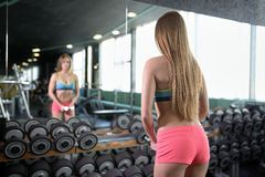Sporty girl doing exercise with dumbbells in gym opposite to mirror Royalty Free Stock Image