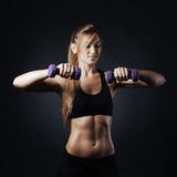 Sporty girl doing exercise with dumbbells. Sport picture with fitness woman on it Royalty Free Stock Images