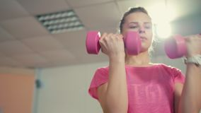 Sporty Girl is Doing Exercise with Dumbbells on at Training in the Gym. Young Beautiful Girl is Doing Sport Exercise with Dumbbells on Mini Trampoline at stock video footage