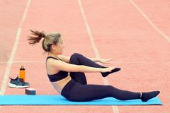 Sporty girl doing leg stretching sitting on a fitness mat at the stadium. Group and individual sport activities in the fresh air. royalty free stock images