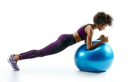 Sporty girl doing plank exercise on gymnastic ball. Royalty Free Stock Images