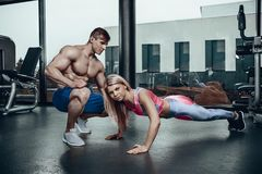 Sporty girl doing plank exercises with support of her personal trainer. royalty free stock image