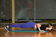 Sporty girl doing push-ups at gym Royalty Free Stock Photos