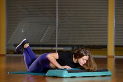 Sporty girl doing push-ups on platform for an aerobics step Stock Photo
