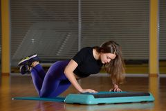Sporty girl doing push-ups on platform for an aerobics step Royalty Free Stock Images
