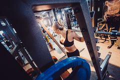 Sporty girl doing some squats with a barbell in a gym. Blond girl in a gym doing lunges with a barbell. From above view Royalty Free Stock Images