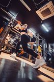Sporty girl doing some squats with a barbell in a gym. Blond girl in a gym doing lunges with a barbell close Royalty Free Stock Photos