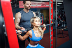 Sporty girl doing squat exercises with assistance of her personal trainer at gym. Royalty Free Stock Image