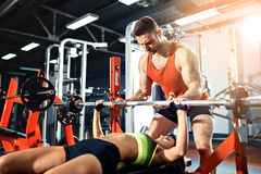 Sporty girl doing weight exercises with assistance of her personal trainer at gym. Sporty girl doing weight exercises with assistance of her personal trainer at Royalty Free Stock Image