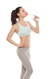 Sporty girl drinking water from a bottle after a workout, fitness training, isolated on white background Stock Photos