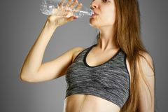Sporty girl drinking water from clear plastic bottles Stock Images