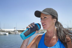 Sporty girl drinking water outdoors. Close up of a fit girl drinking water after a workout Royalty Free Stock Photography