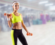 Sporty girl with dumbbells in fitness club Stock Photo