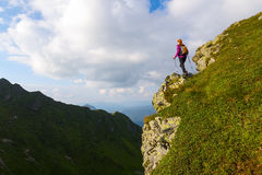 Sporty girl at the edge of precipice high on the mountains Stock Photo