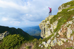 Sporty girl at the edge of precipice high on the mountains Royalty Free Stock Image