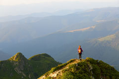 Sporty girl at the edge of precipice high on the mountains Stock Photography